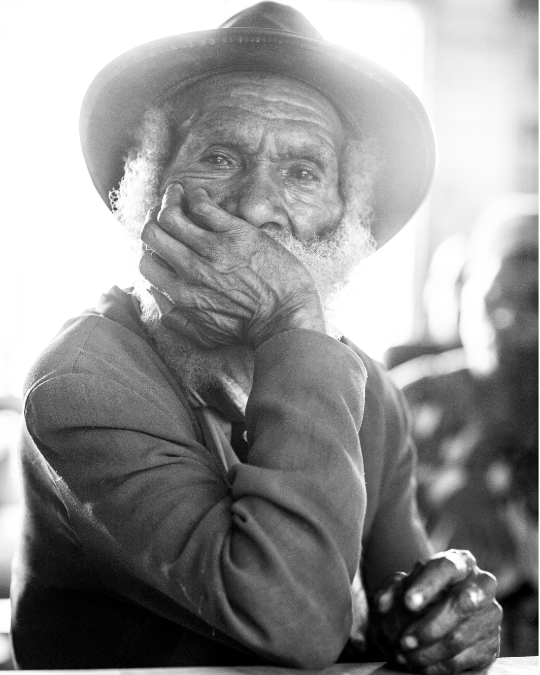 A tribal elder in rural Enga Provence, Papua New Guinea.  Sitting for hours listening to external monitors discussing the future of his children education.