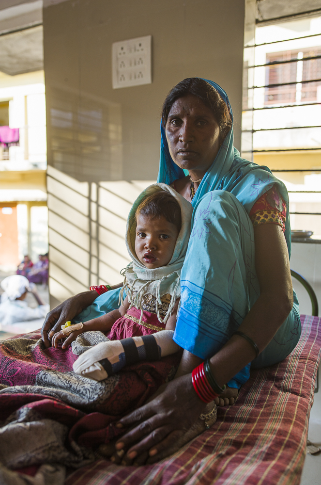 A mother tends to her child in the recovery ward.