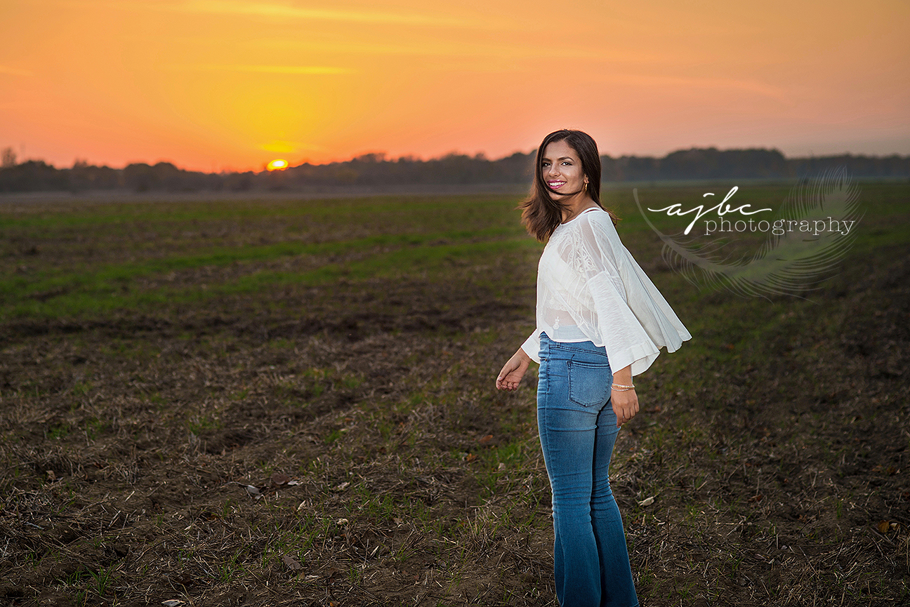 outdoor senior photoshoot senior fashion senior in field with sunset blue jeans country field michigan senior photographer cardinal mooney high school senior girl photoshoot.jpg