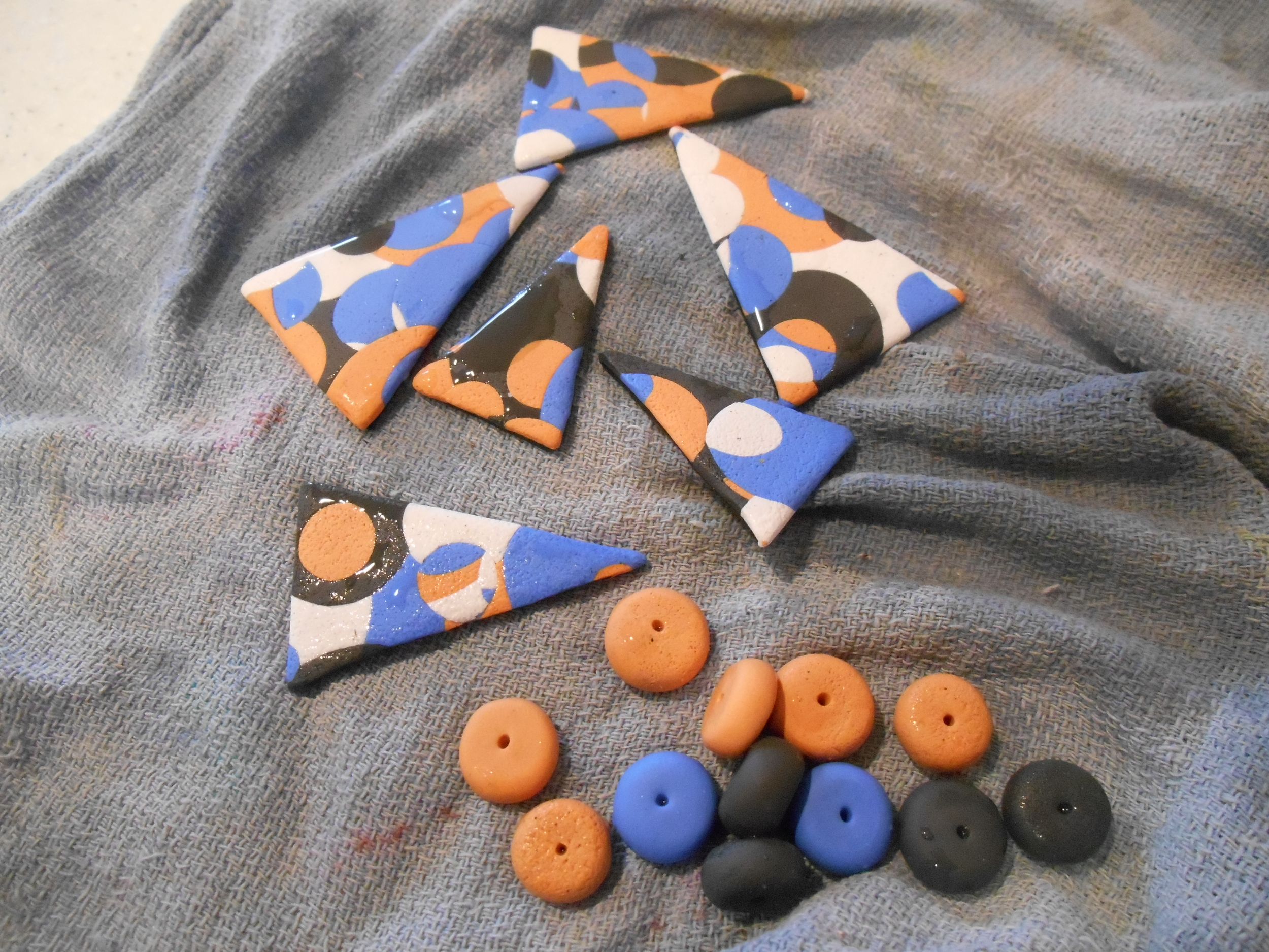 Here are the fired and bathed pieces- I decided to make some textured beads as well.  I think I'm going to need them for the overall length.  I went with a stone gray, a periwinkle blue, some soft peach and white.  I hand blended to achieve my colors.