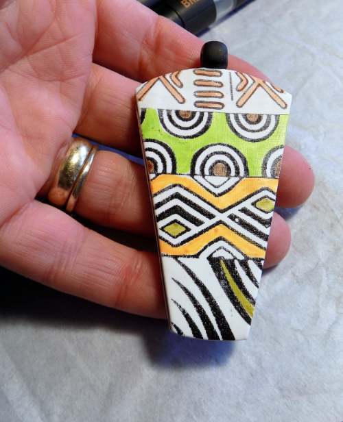 A cool black and white tribal pendant with pops of color from Chameleon pens!
