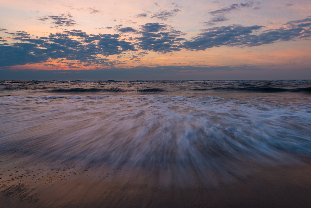 A typical seascape a sunrise captured with an ultra wide-angle lens. I waited until a wave broke just before tripping the shutter to capture a dramatic foreground complimented by the sunrise sky.