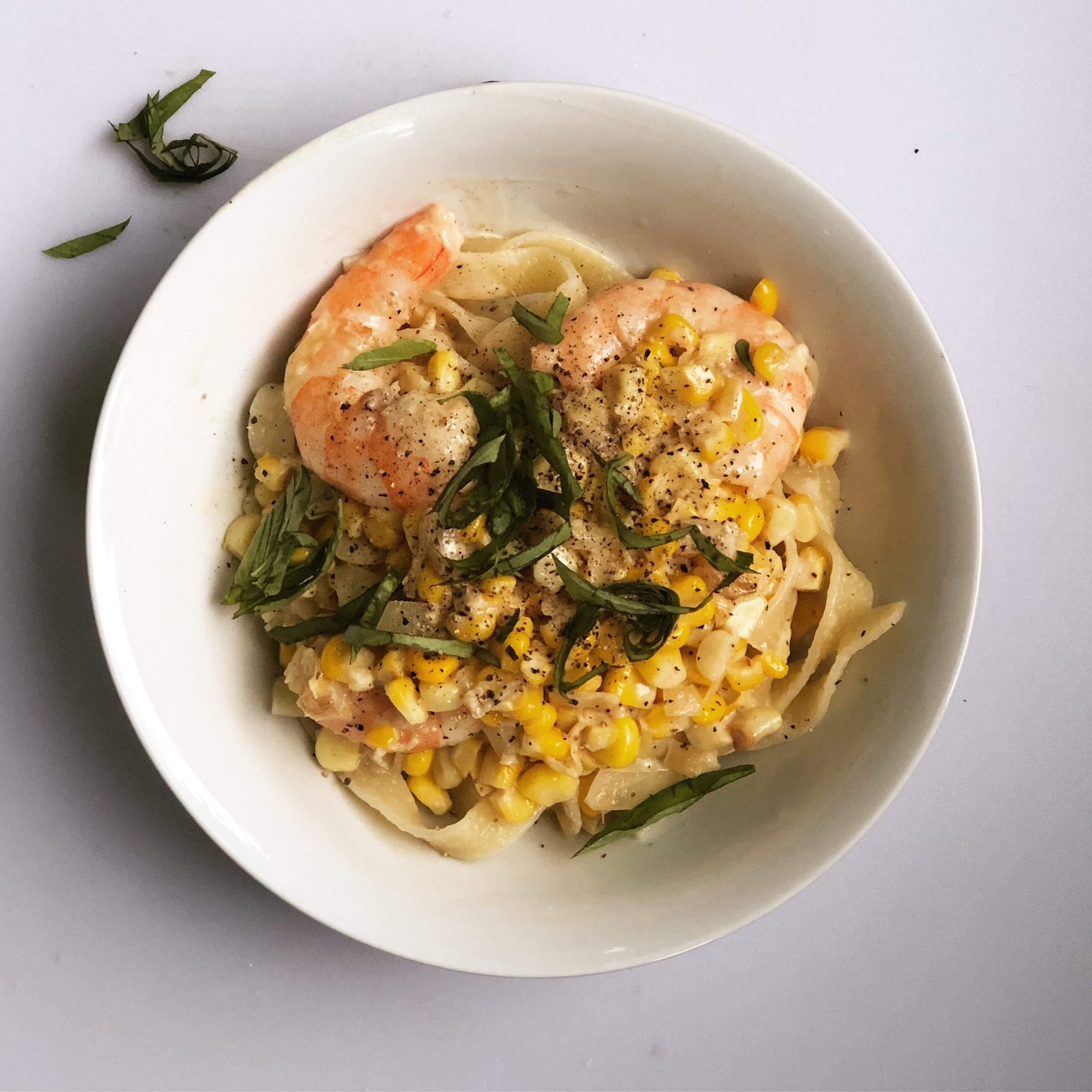 improv. corn & shrimp alfredo over tagliatelle, topped with garden basil and cracked pepper.