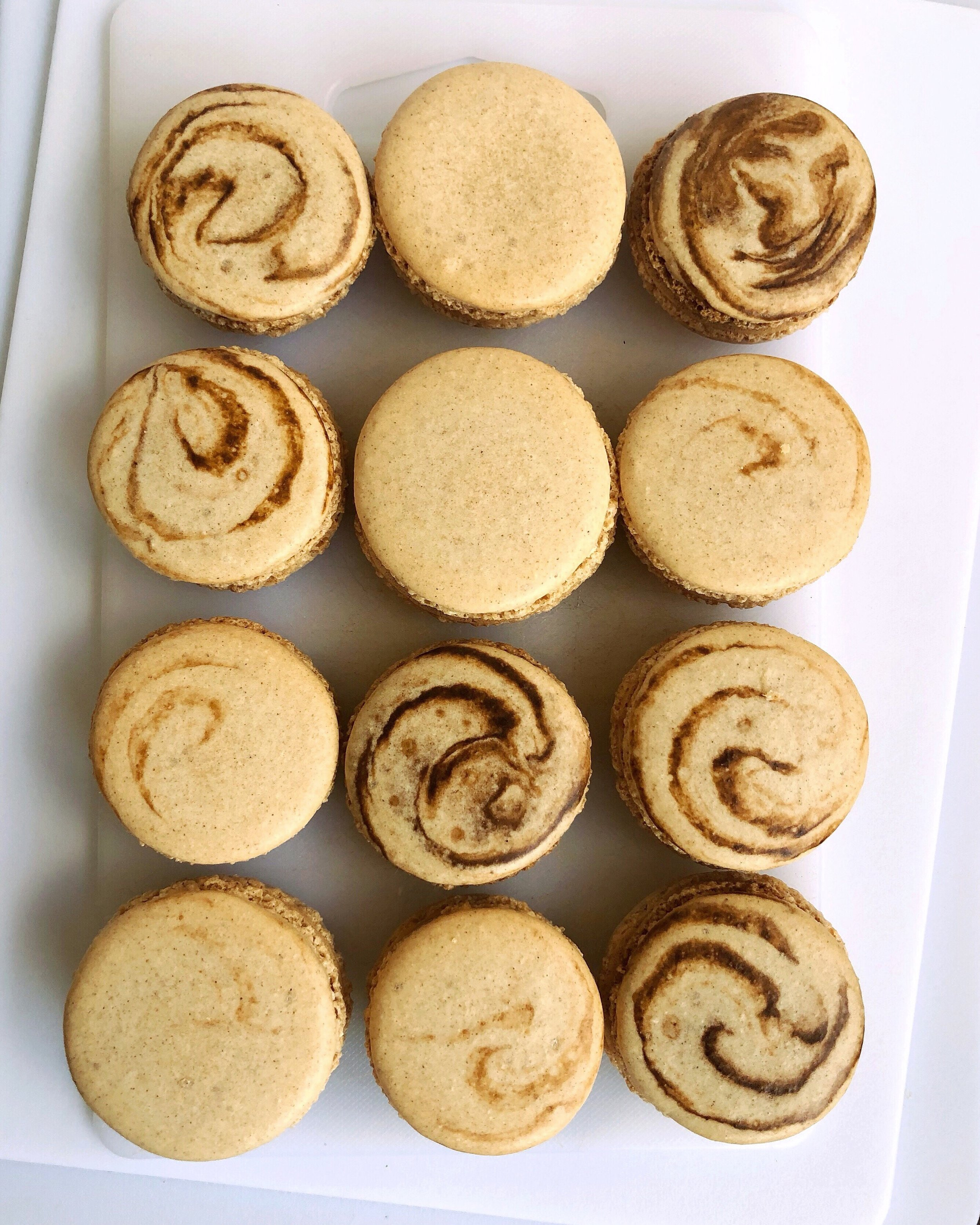 "macaron experiment. ""cinnamon roll"" macarons - cinnamon shell with cream cheese frosting."