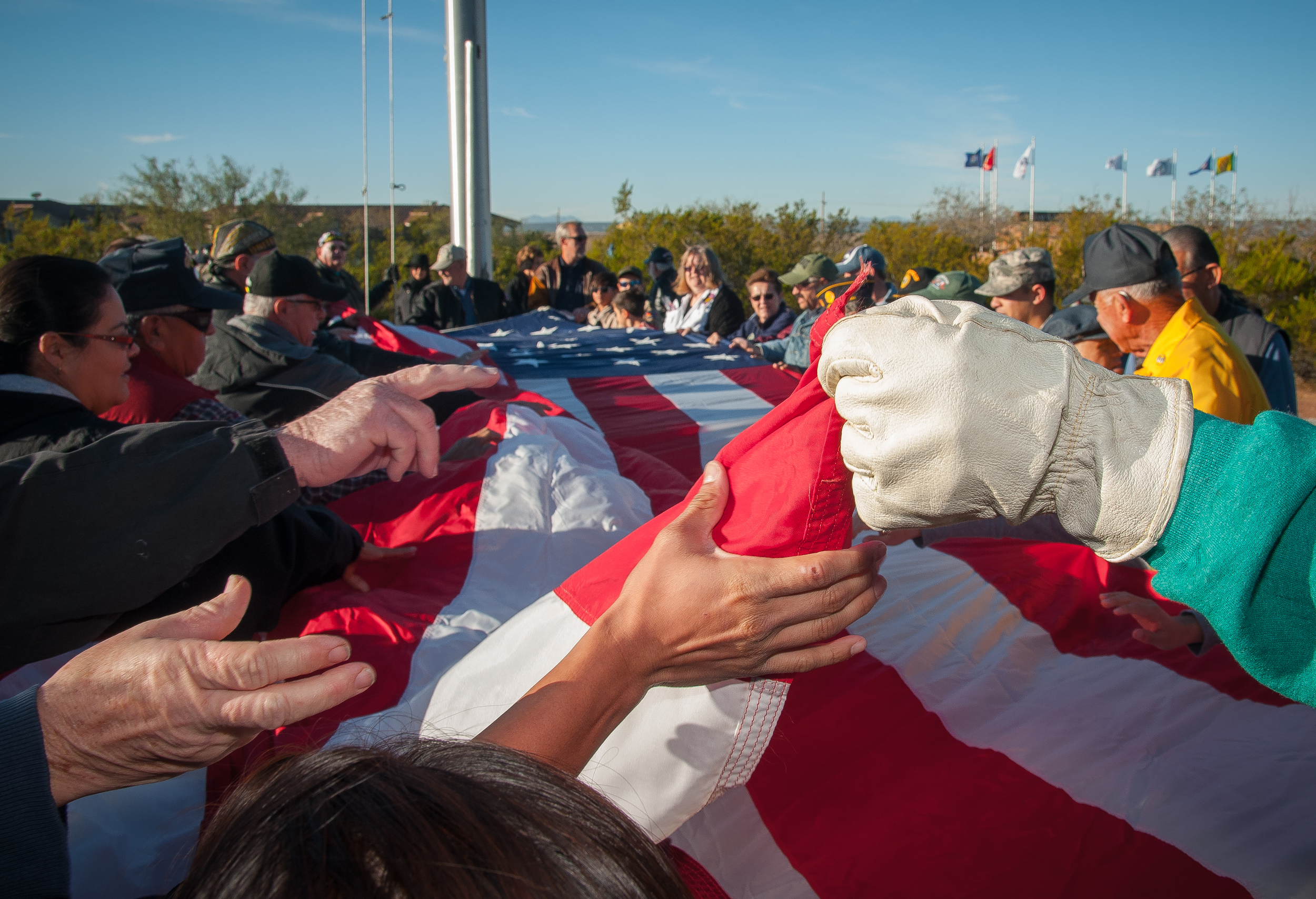 Veterans and visitors to Veterans Memorial Park on Veterans Day unfurl Las Cruces' garrison flag prior to it being raised.