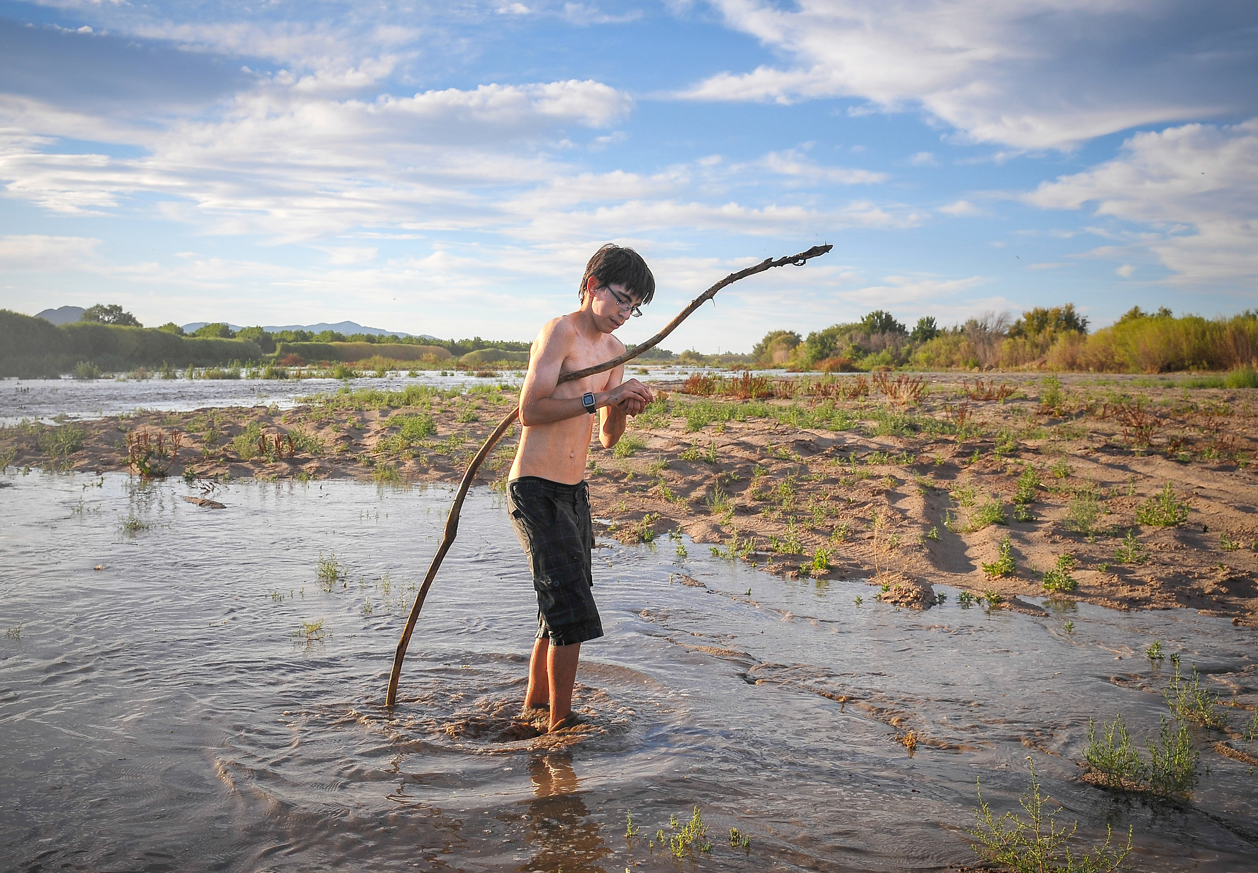 14-year-old Las Cruces native Domingo Cadena searches for toads on the Rio Grande by Bosque State Park in New Mexico as water seeps into the river for the first time this year on Wednesday, May 27th, 2015. The water, which was released by Elephant Butte and Caballo Dams, is expected to reach El Paso on Friday, May 29th, and after that Mexico.