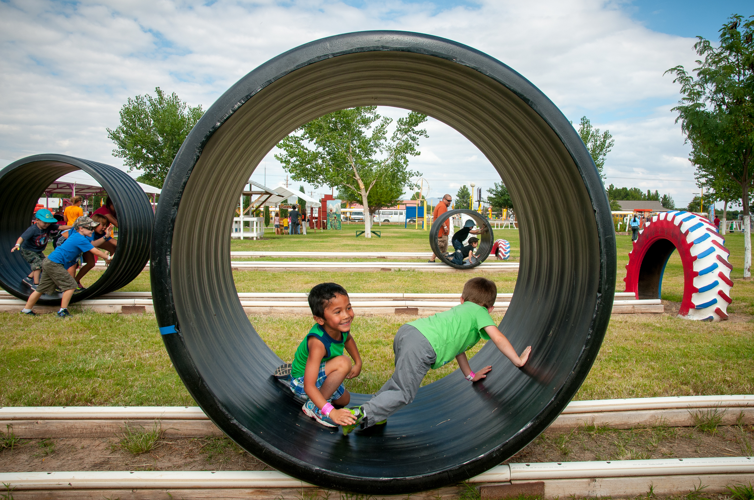 "4-year-old Discovery Child Development Center students Christian Schaper, left, and Riley Francis have fun in a ""hamster wheel"" at the Mesilla Valley Maze."