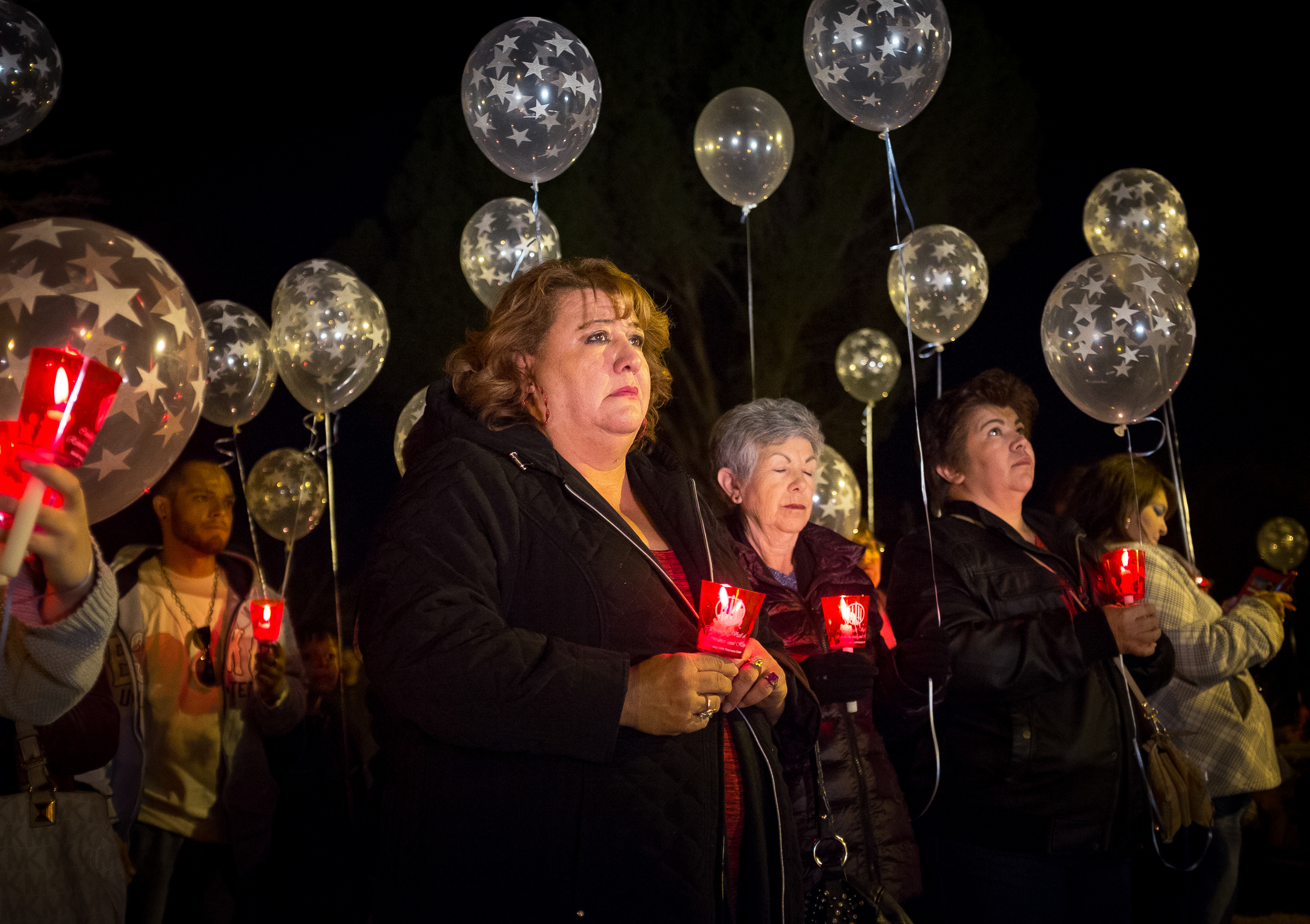 Cynthia Rivera, center, one of approximately 100 people at a Vigil of Remembrance and Hope for DWI and Homicide Victims at Pioneer Park on Saturday evening, holds a candle in remembrance of her husband and two children killed in an accident involving a drunk driver in 1995.