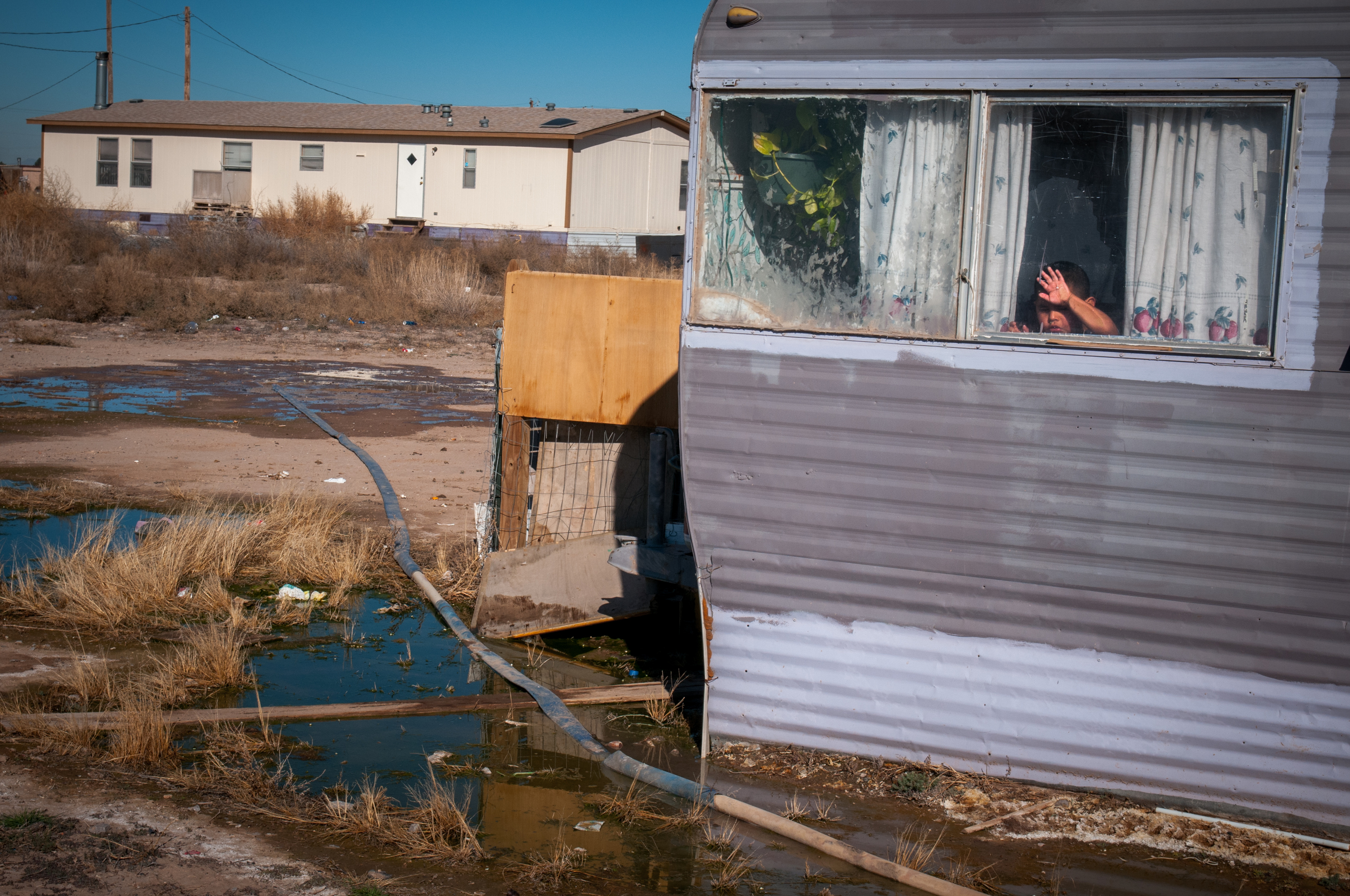 A boy looks out from a trailer as raw sewage seeps out from the ground.