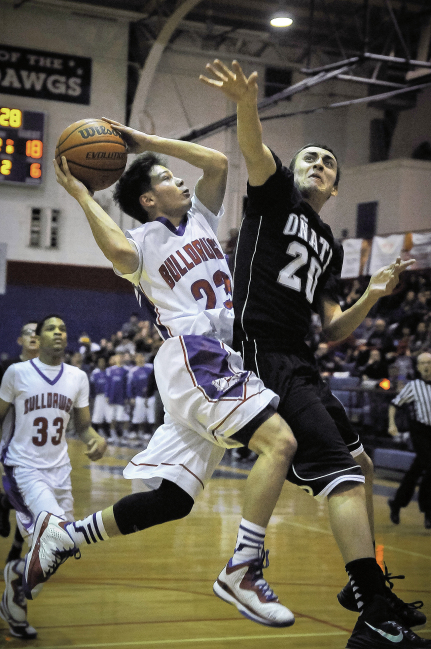 Las Cruces High School guard Mike Uribe shoots over Oñate High School's Ed Ramirez.