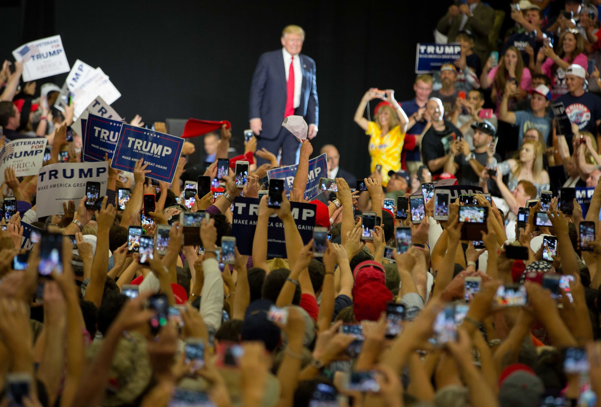 People inside the Albuquerque Convention Center takes photos of presidential candidate Donald Trump as he walks towards a podium, May 24, 2016.