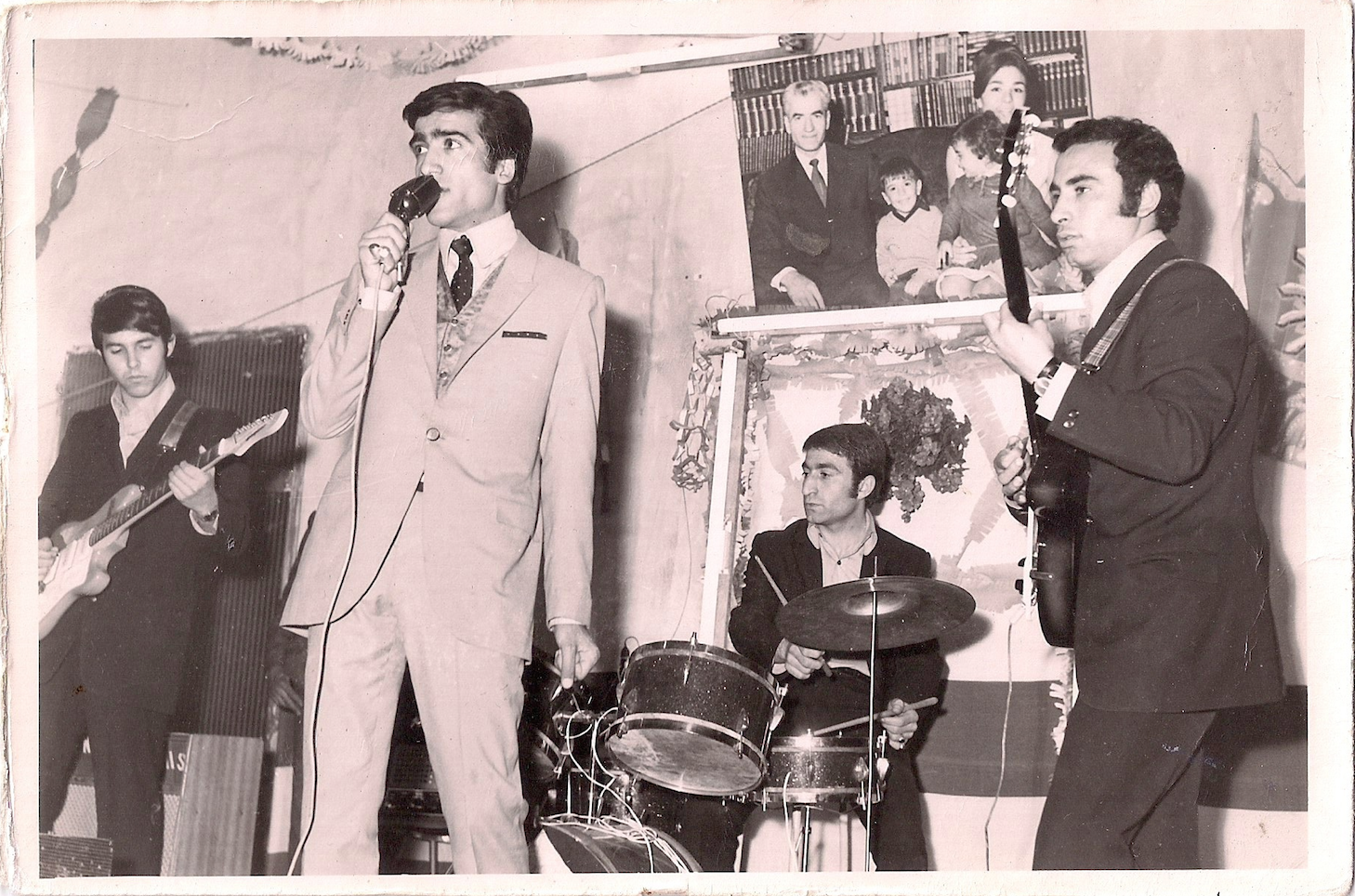 Joe's father (middle) playing his only rock show with his still best friend on guitar (right). Despite how it may look, the performance was apparently awful. In the background photo is the Shah with the royal family.