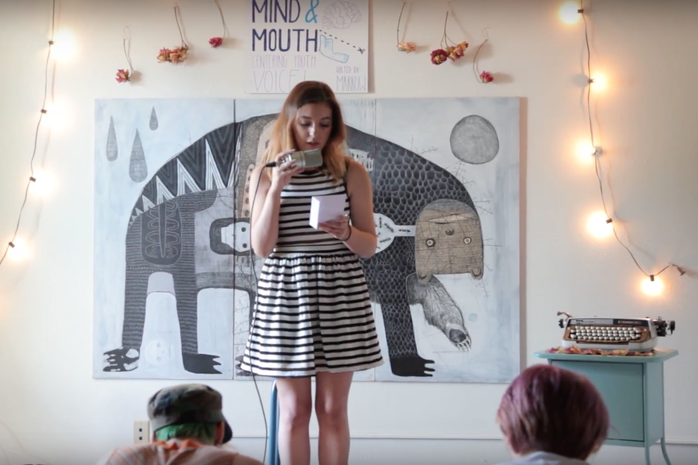 Kylin performs in front of one of Jesse's paintings at an open mic.