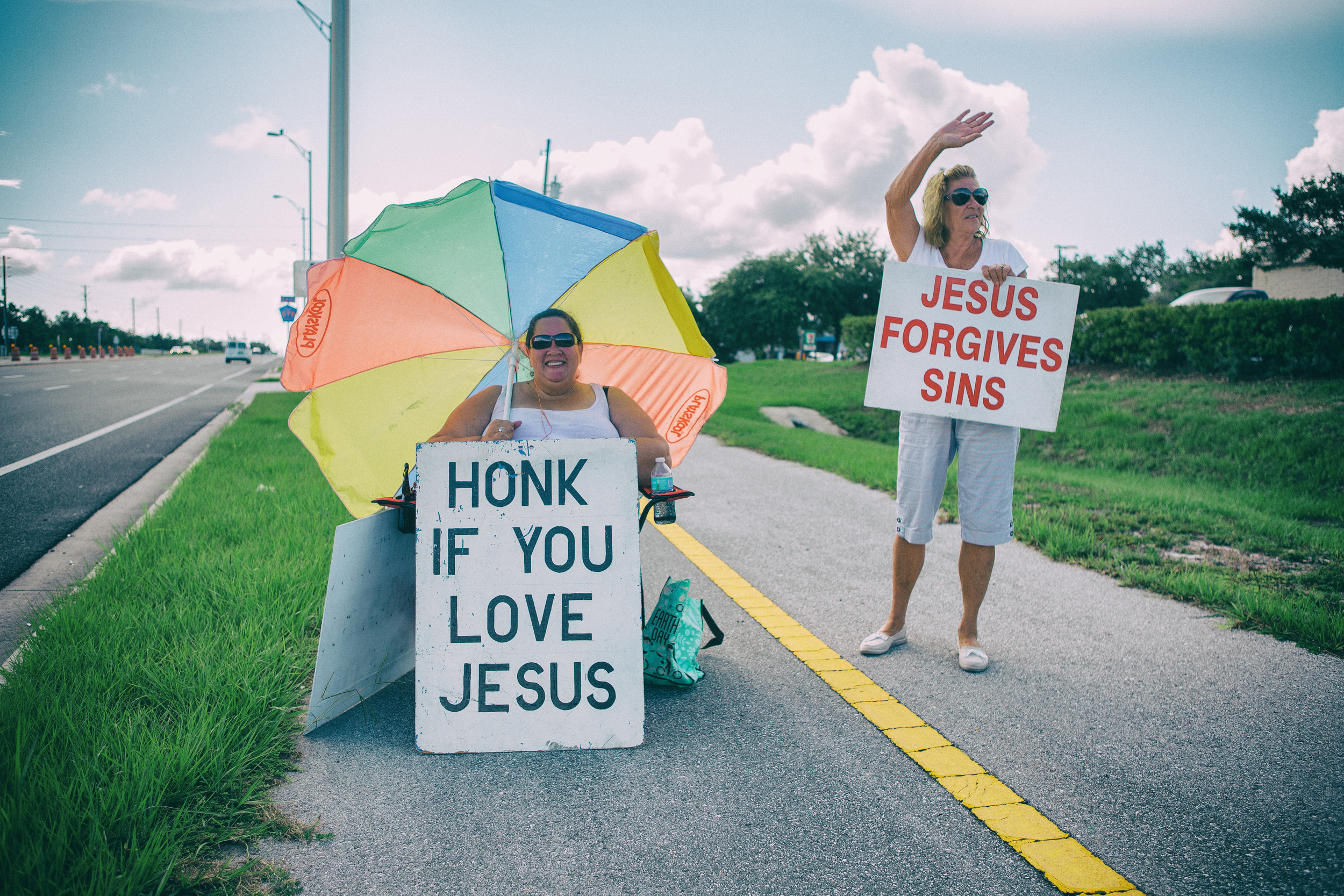 I passed this woman on Hwy 19, just outside of Clearwater, FL, then made a U-turn to grab the shot. She was honored and so was I. Everything about this shot, her smile, the leading lines, typography, colorful umbrella, and friend framed perfectly in the clouds put this one on the short list.
