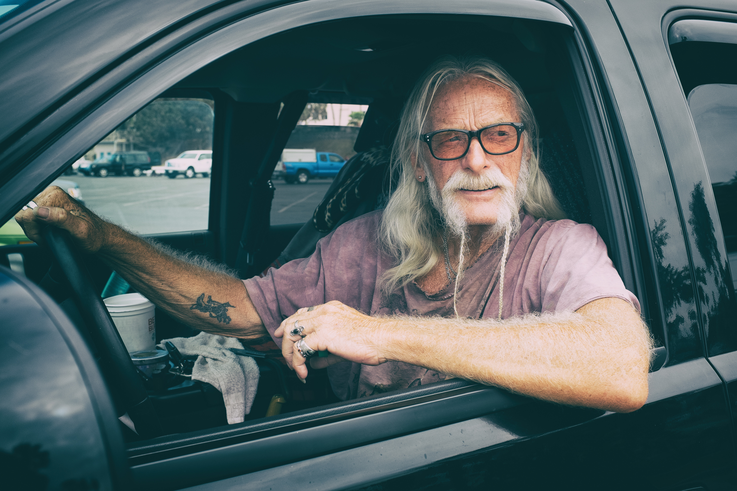 "Somewhere in Santa Monica, I passed this man, looking at the passerby's from his truck. I stopped and asked for a shot, he said, ""Usually people try to sneak around and grab a picture and I don't know why they don't come up and talk to me."" I had the shot before he finished his sentence."
