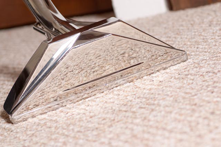 A close up view of a vacuum cleaning a carpet.