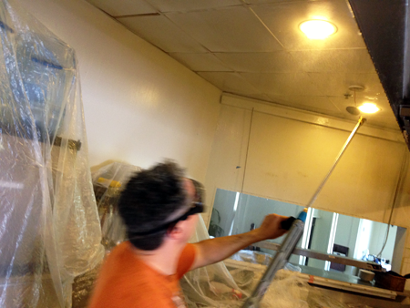 A man with glasses on cleaning light fixtures of a commercial property.