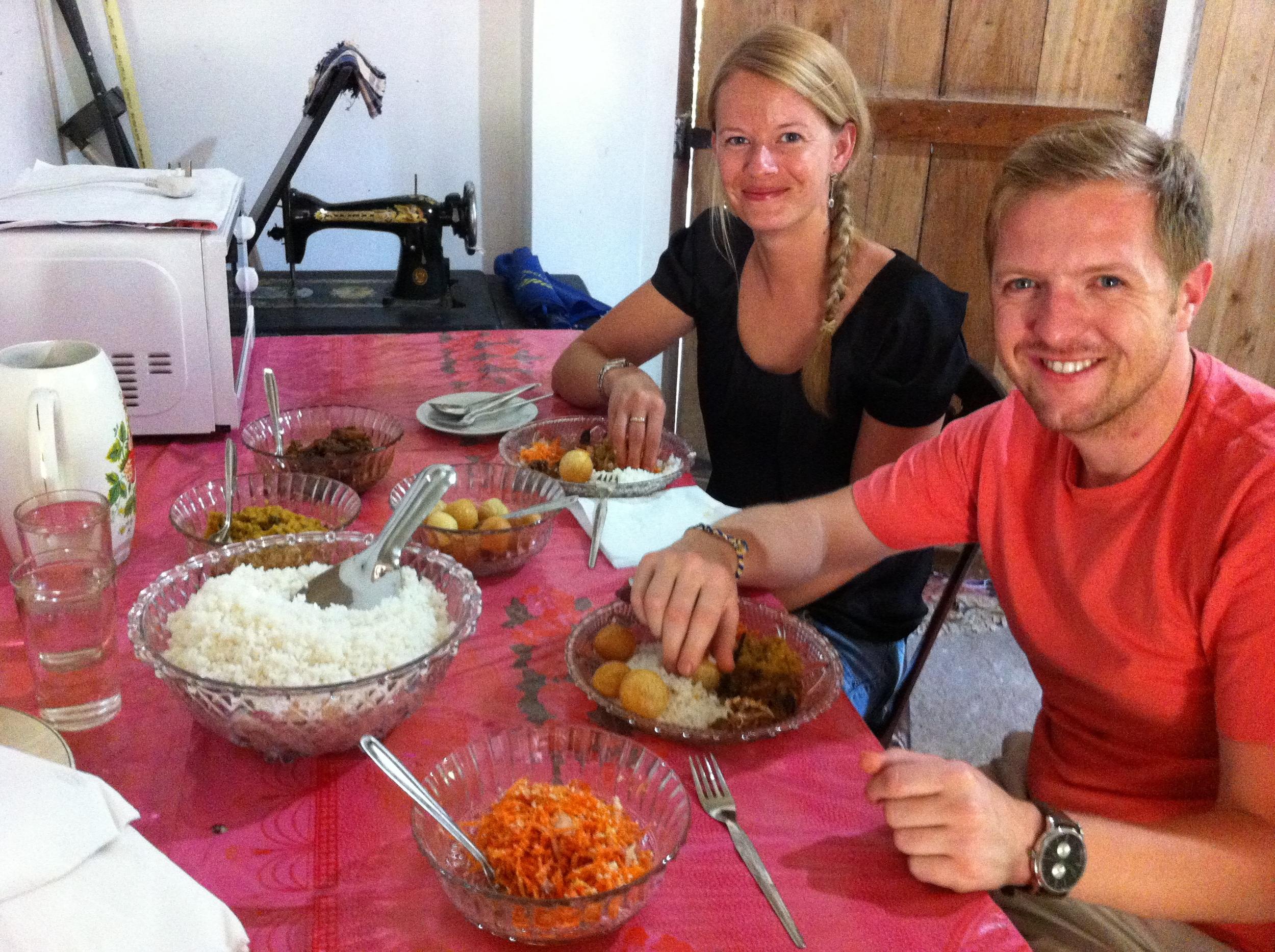 Invite to Paradise founders, and husband and wife, Reece and Claire Turvill in rural Sri Lanka having local rice and curry.