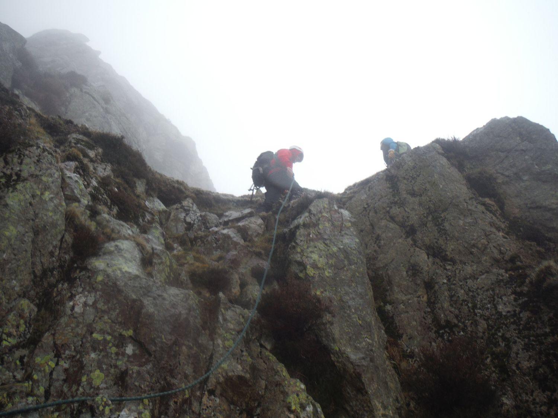 a mountaineer reaching the top of a scramble - Chris Ensoll Mountain Guide