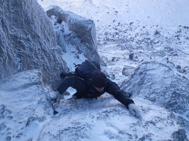 A climber scrambling up a snowy gully - Chris Ensoll Mountain Guide