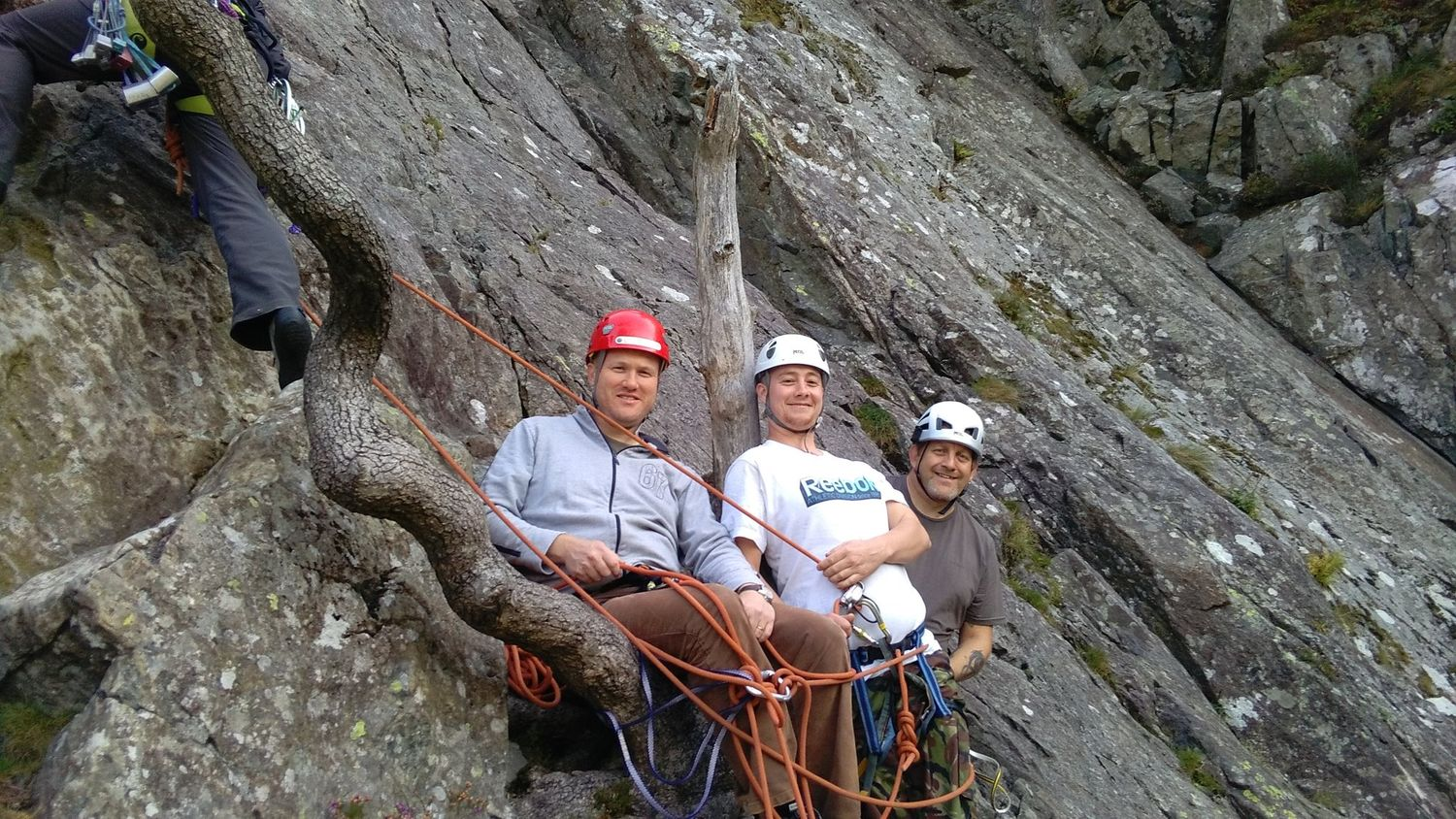 A group of clients belaying at the bottom of a single pitch rock route in the Lake District - Chris Ensoll Mountain Guide