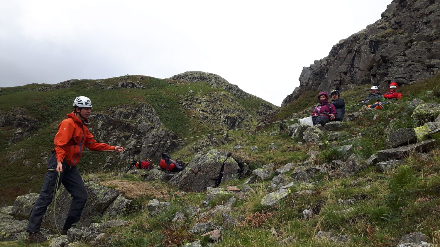 Mountain leader training candidates using a safety rope on steep ground