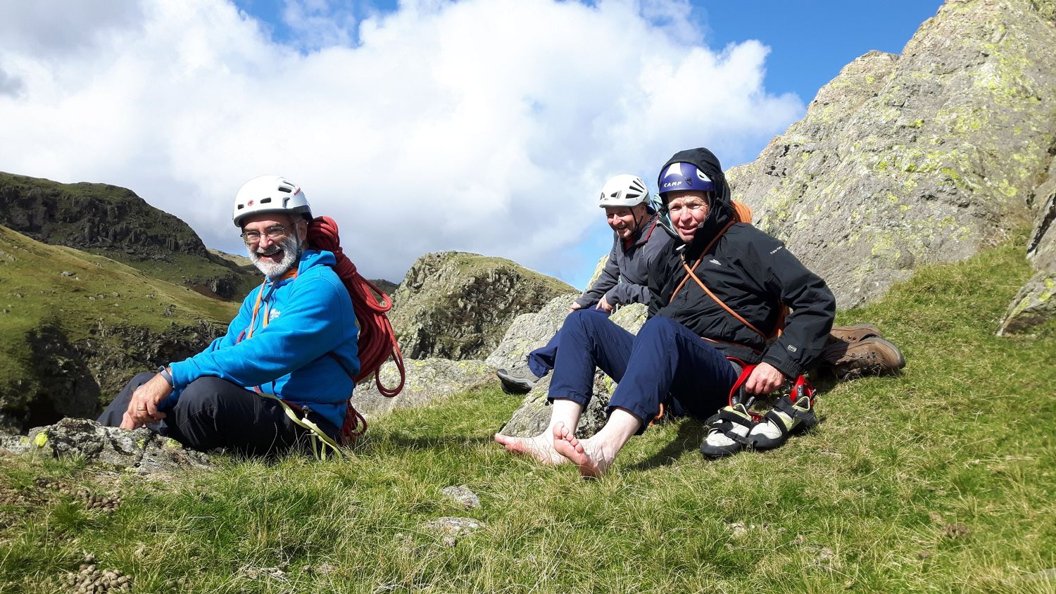 A group of clients savouring success at the top of a multi pitch rock climb in the Lake District - Chris Ensoll Mountain Guide