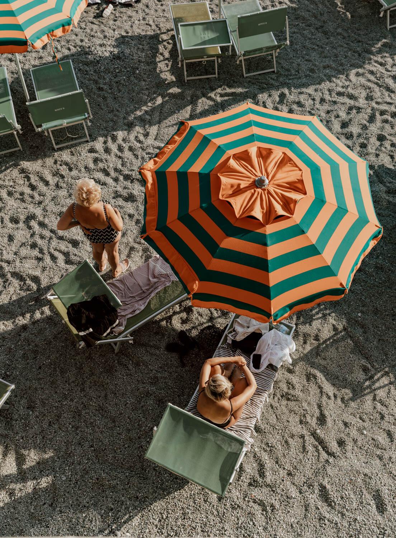 在蒙特罗索海滩的猩猩和绿色遮阳伞