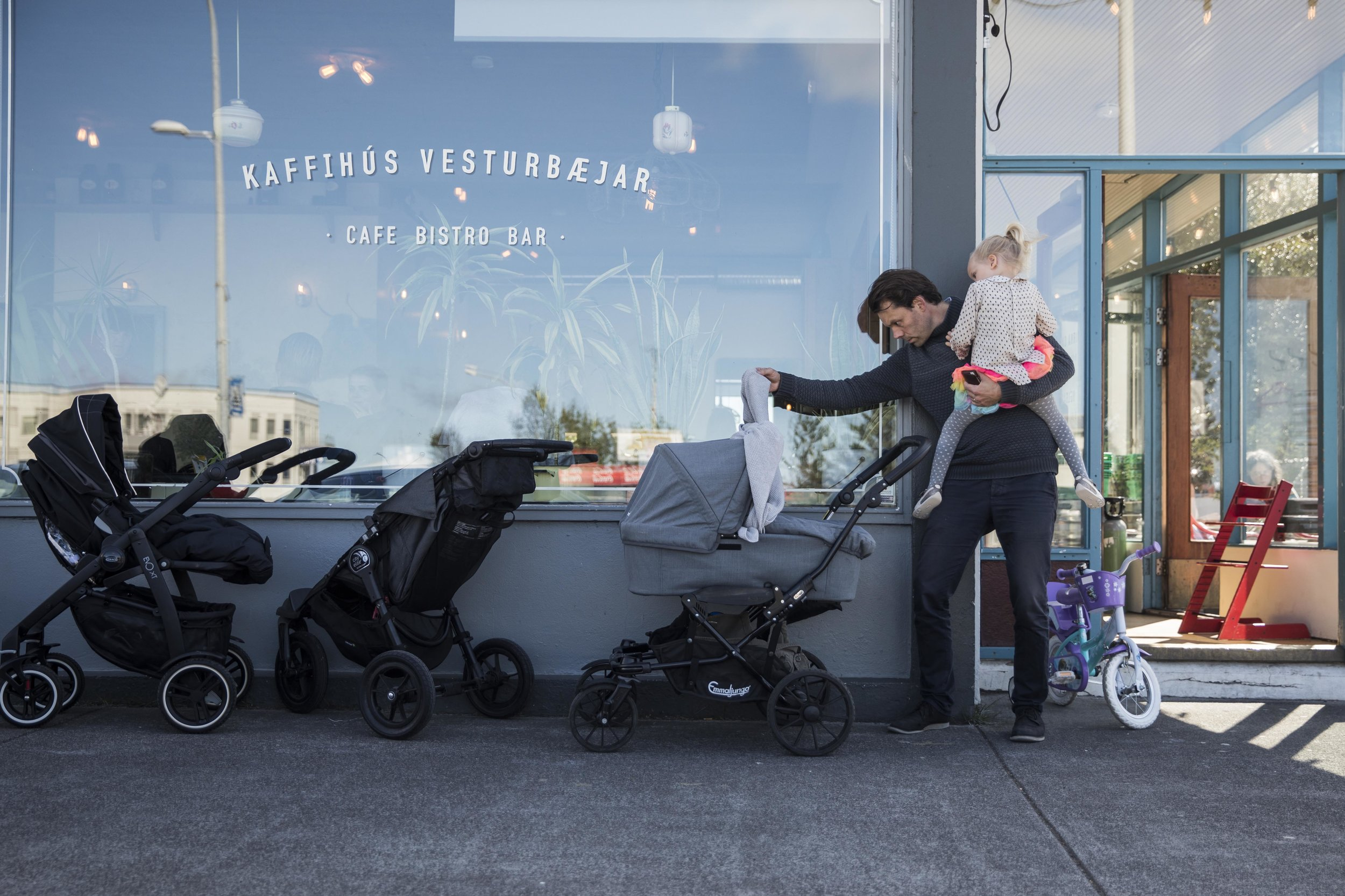 Björn Thors checks on his twin babies while he and his five-year-old daughter, Bryndis, have lunch at a cafe near their home in Reykjavik.