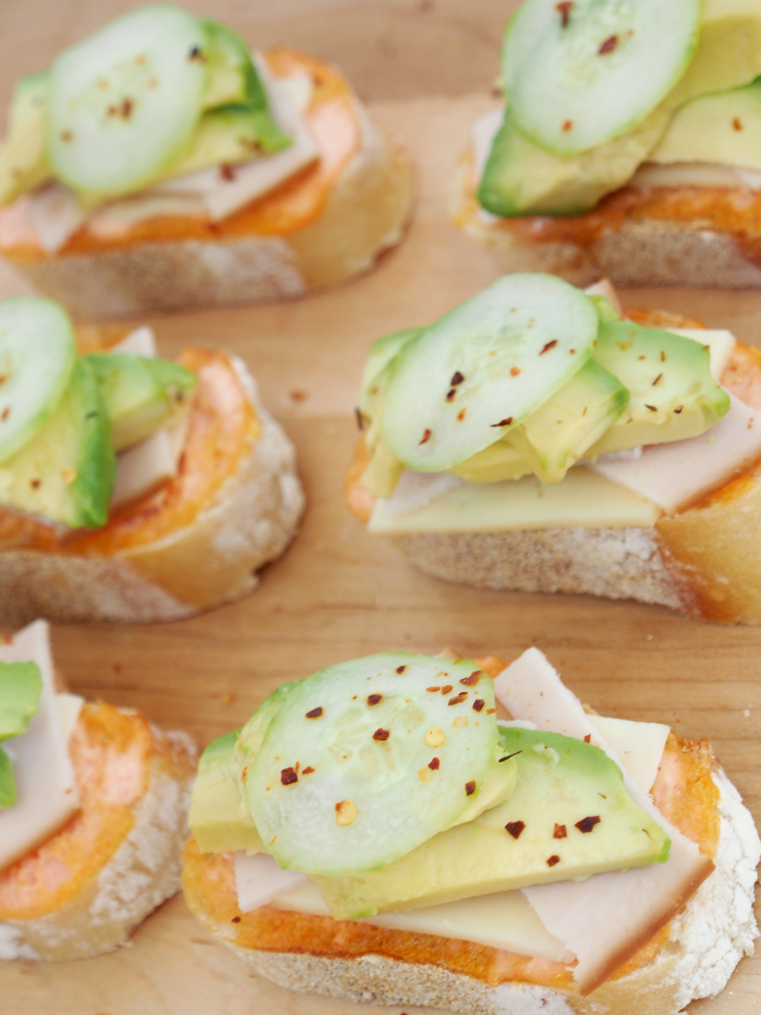 Close-up view of the mini open faced turkey avocado sandwiches.. YUM.