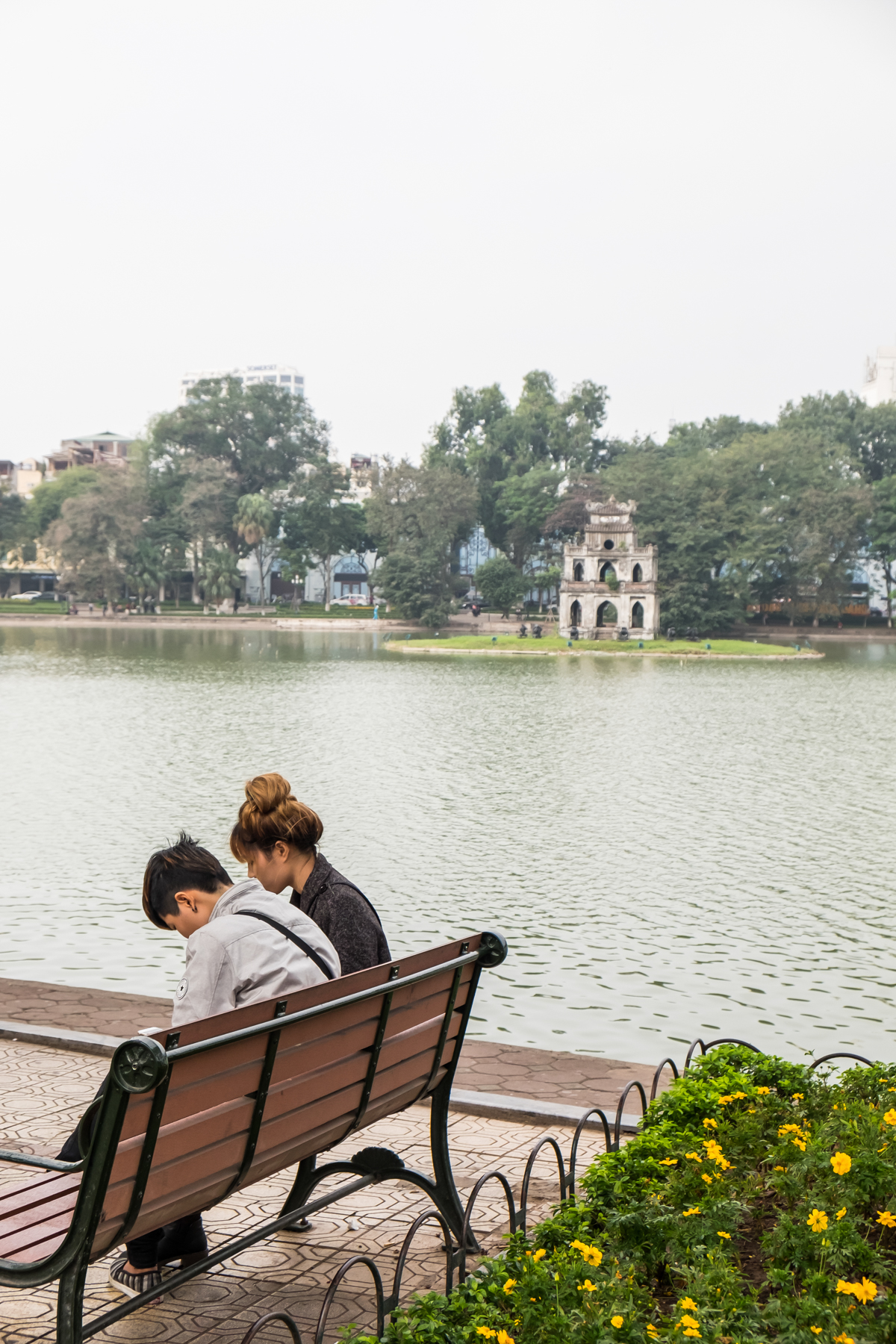A couple sits by Hoan Kiem Lake in Hanoi, Vietnam - Tháp Rùa also called Tortoise Tower in the distance.