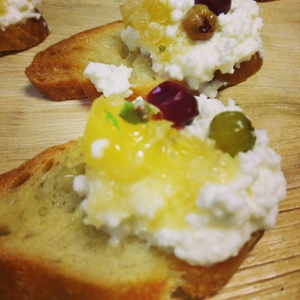 Crostinis with fresh cheese, pickled blueberries, honeycomb, and pine tips by home.made.