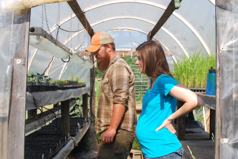 Nathan and Simone Brett inspecting pumpkin seedlings. Photo by me.