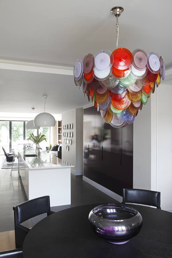 Dining area overlooking kitchen; colorful Murano glass disk chandelier above aubergine blown glass bowl | Knightsbridge London | Savage Interior Design