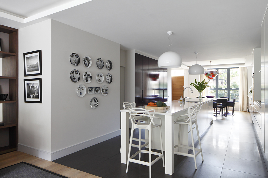 Grouping of Piero Fornasetti plates opposite modern white kitchen island with Knoll bar stools and aubergine cabinetry | Knightsbridge London | Savage Interior Design