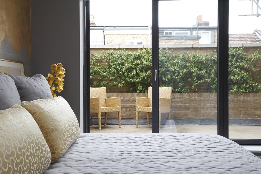 Bedroom with Phillip Jeffries gold metallic wallcovering overlooking patio with B&B Italia chairs | Knightsbridge London | Savage Interior Design