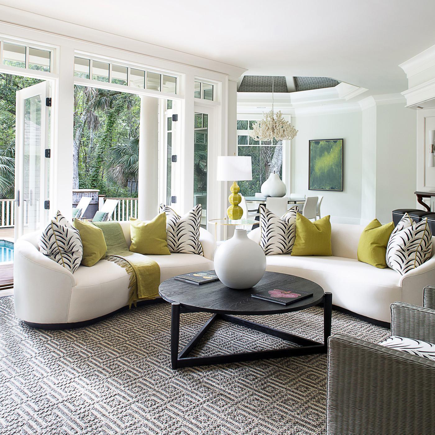 Living room overlooking tropical landscape with pool; Vladimir Kagan kidney shaped sofas | Savage Interior Design