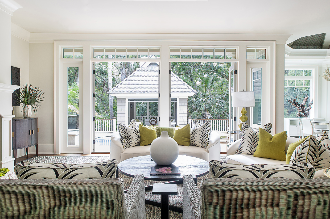 White living room overlooking tropical landscape with pool; Carleton V fabrics; citrus green accents | Savage Interior Design