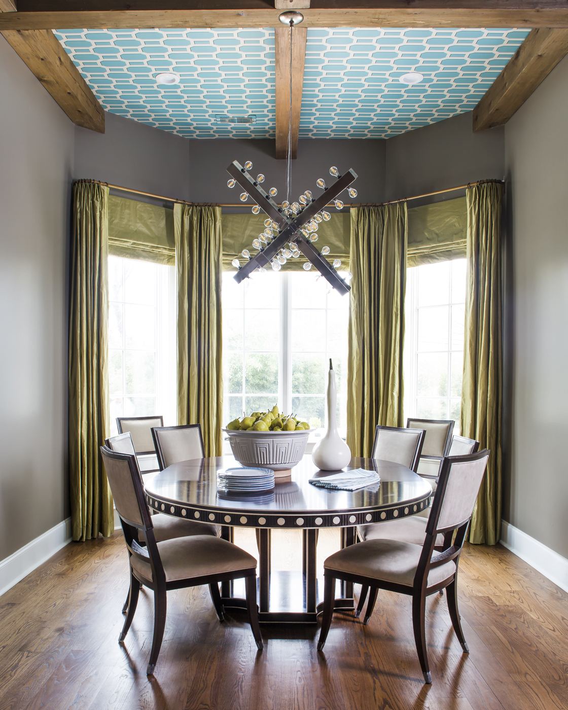 Breakfast room with elegant art deco style round table and chairs; modern x-shape chandelier; turquoise lattice wallpaper on ceiling | Savage Interior Design