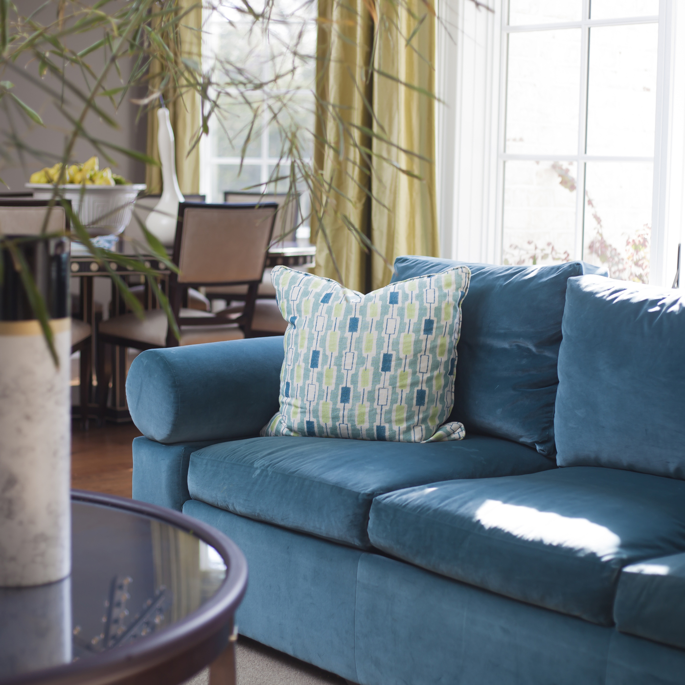 Den with blue sofa and citrus green accents; elegant dining room in background; playful modern pattern pillow | Savage Interior Design