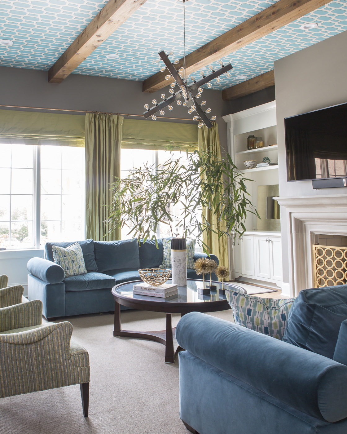 Den with blue sofa and citrus green accents; modern x-shape chandelier; turquoise lattice wallpaper on ceiling | Savage Interior Design