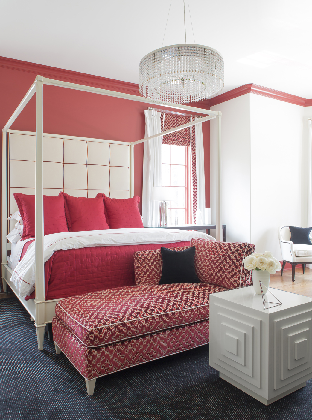 Red, black, and white master bedroom; white canopy bed; tufted upholstered headboard; red chaise lounge; modern cube side table | Savage Interior Design