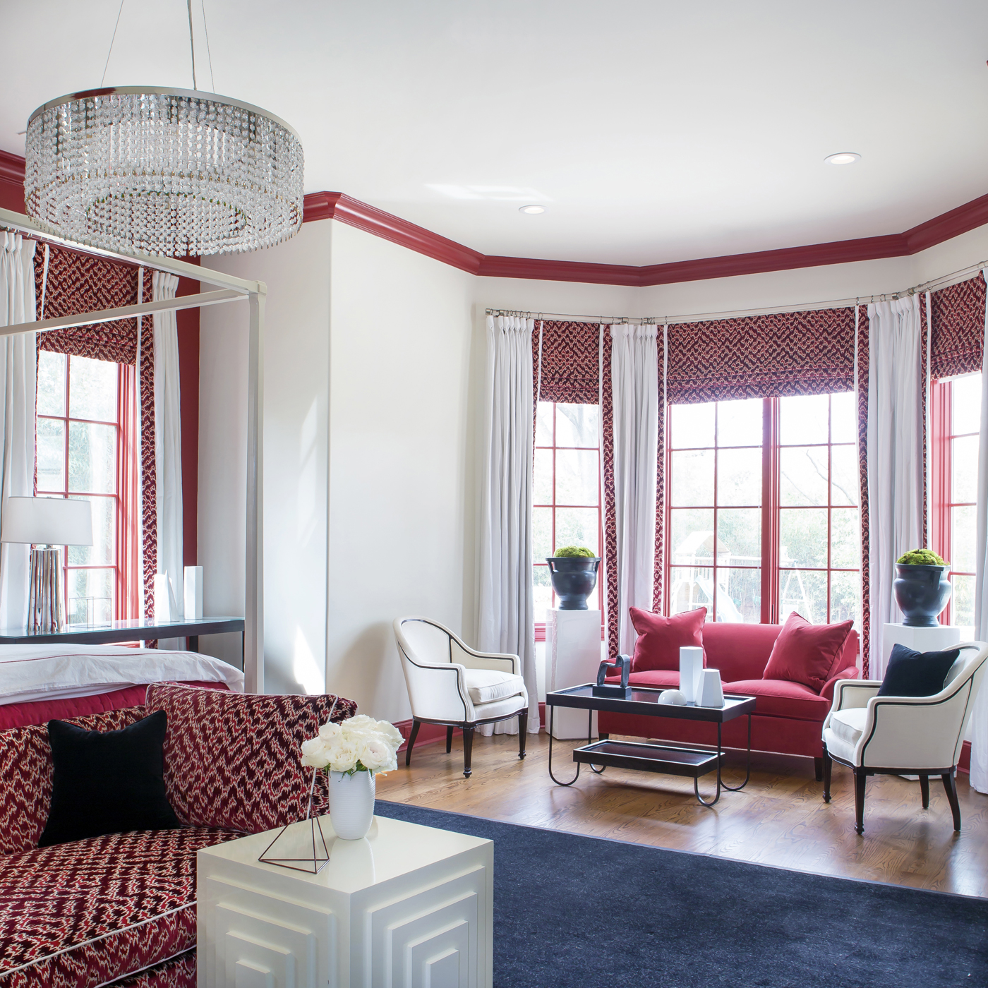 Seating area in bay of red, black, and white master bedroom; red settee; modern round crystal chandelier; red drapery | Savage Interior Design