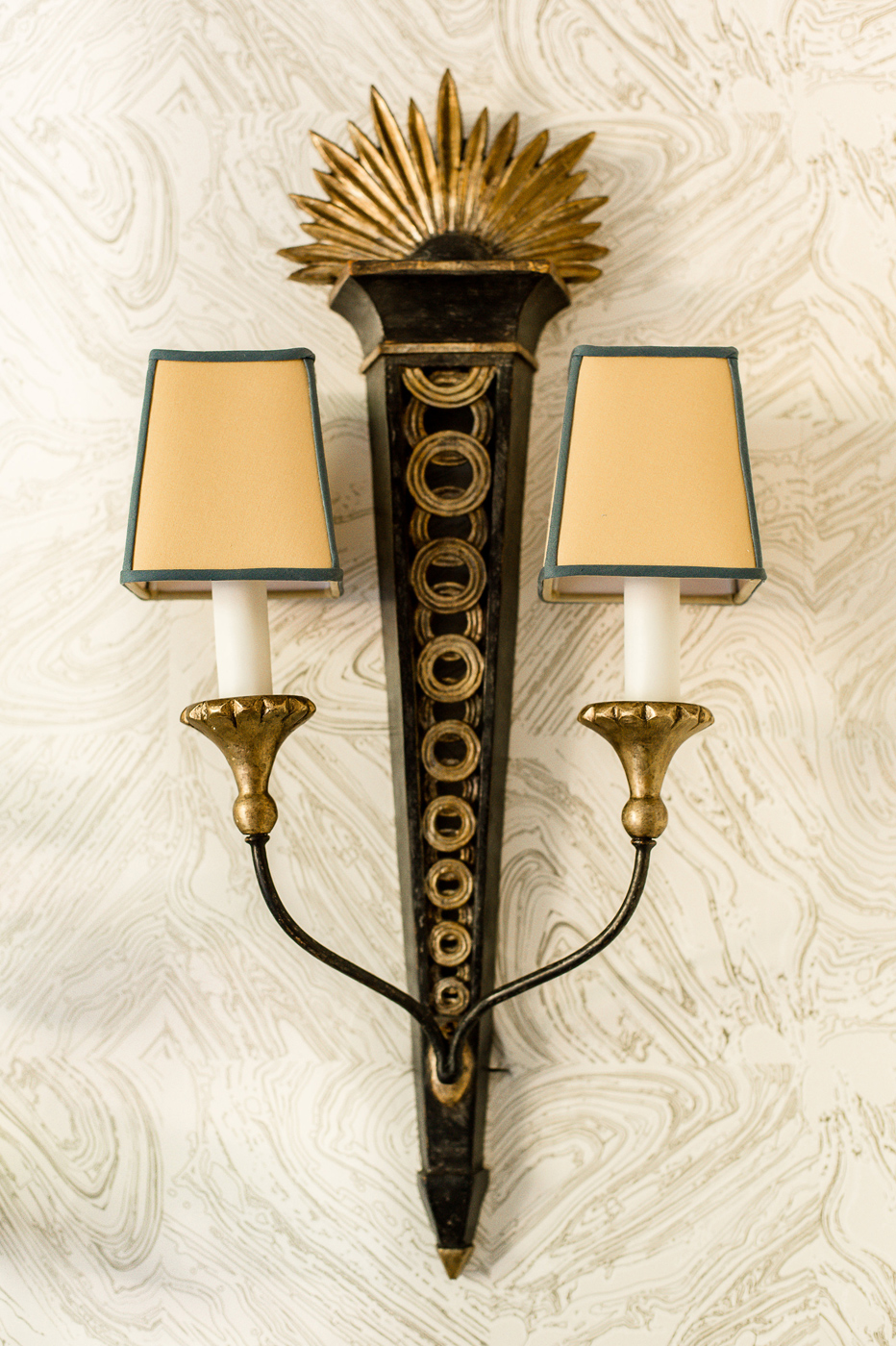 Antique sconce mounted on a swirling cream wallcovering | Savage Interior Design