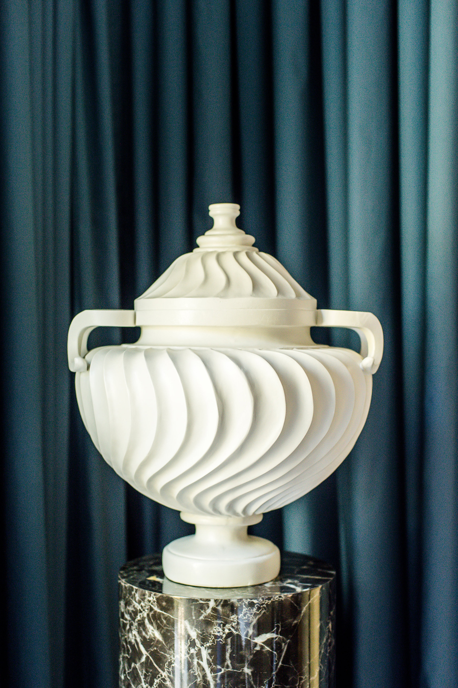 White urn with swirling texture on a marble pedestal | Savage Interior Design