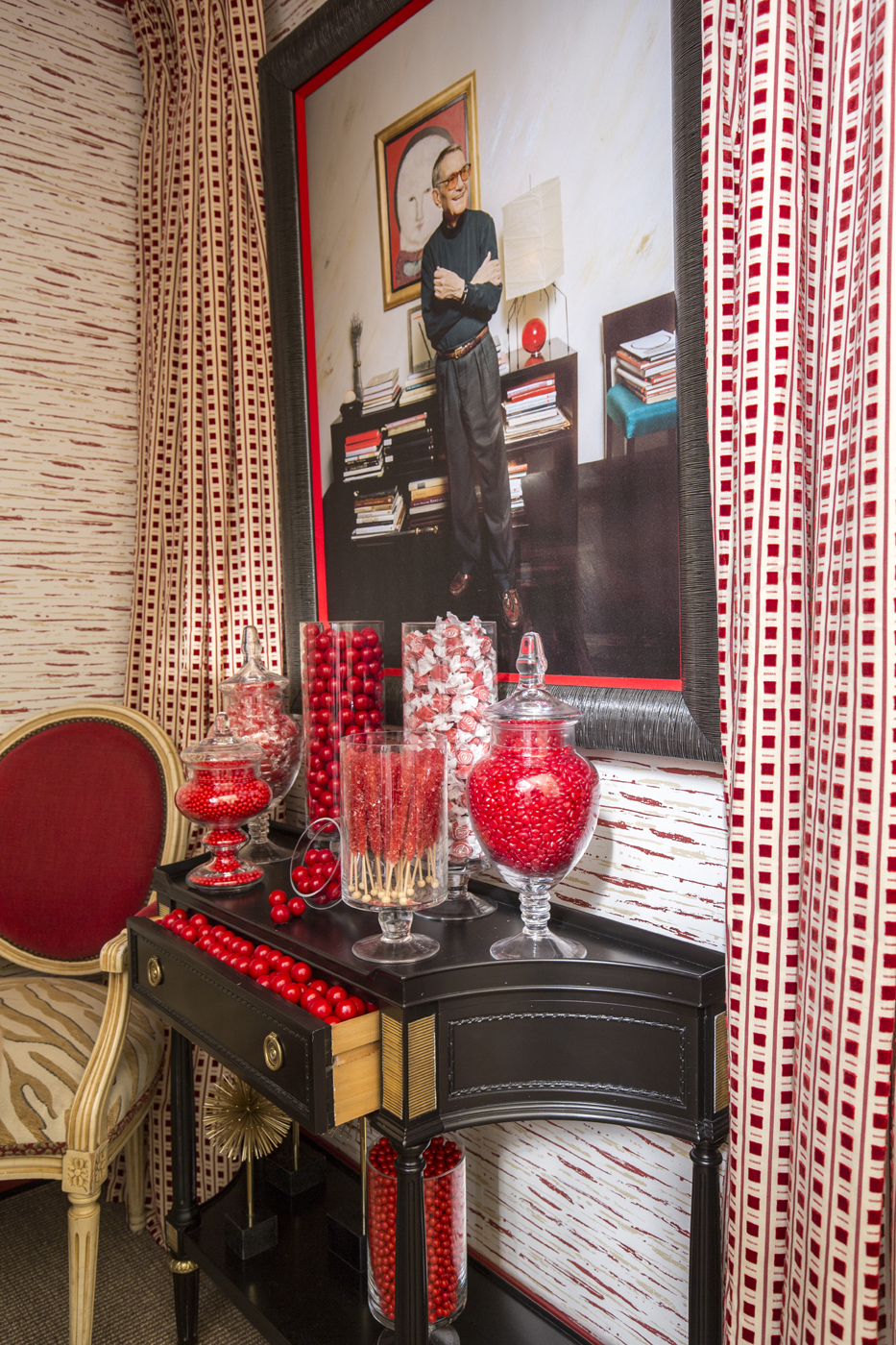 Glass containers filled with red candies serve as decorative accents   Savage Interior Design