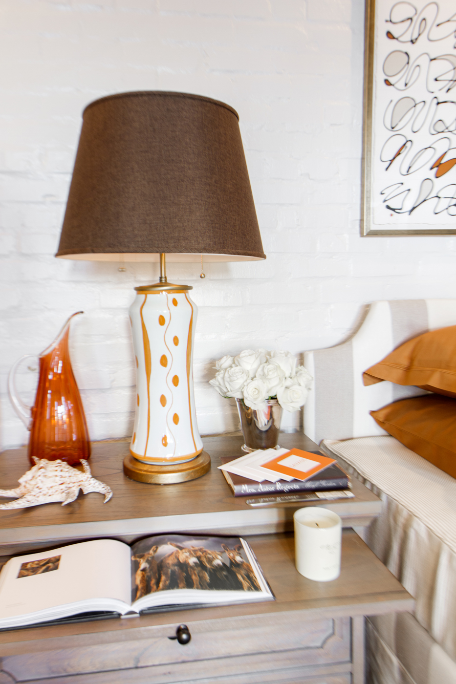 Bedside table accessories with orange and white modern table lamp | Savage Interior Design