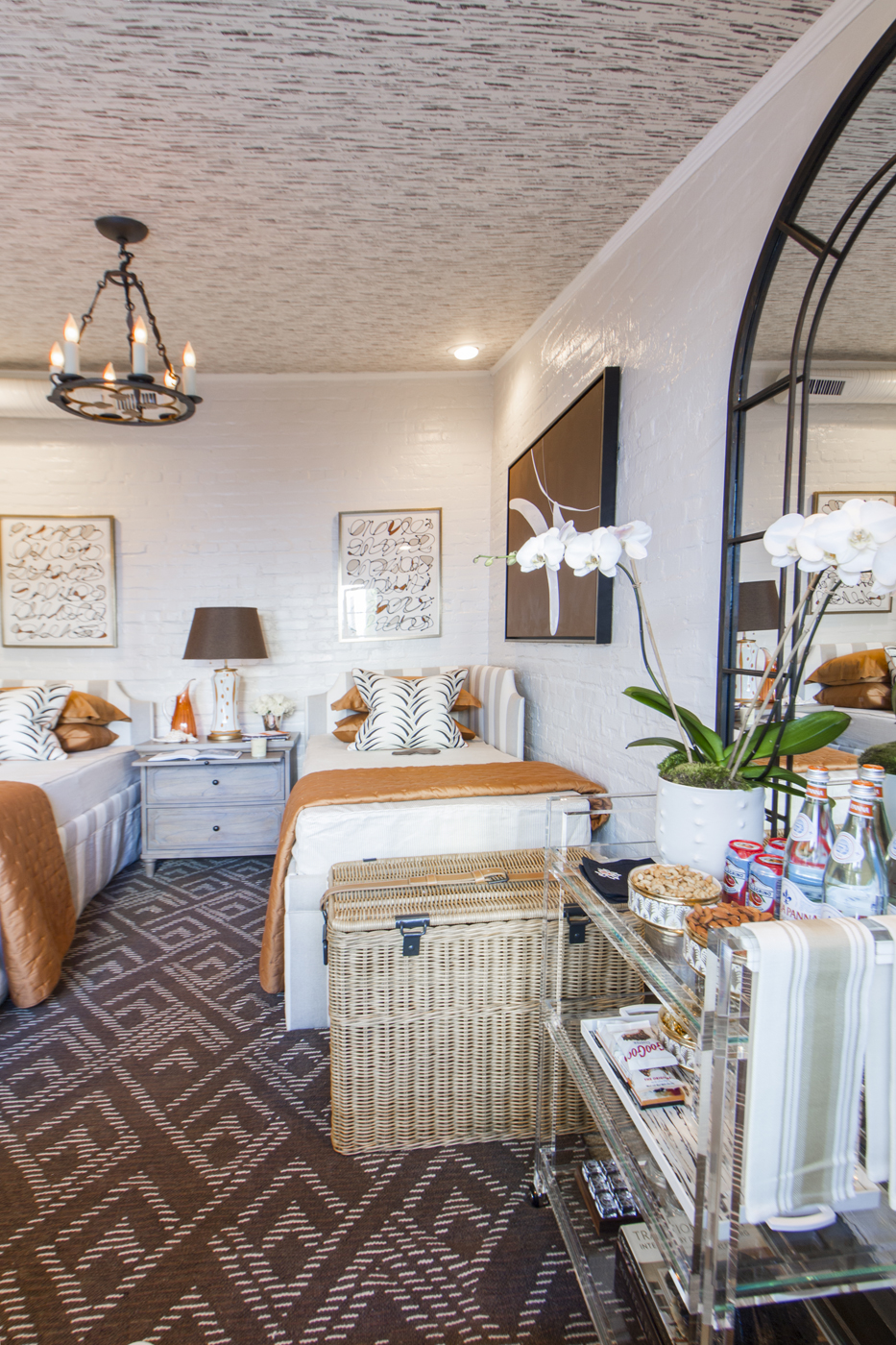 Wicker basket and acrylic lucite table accents in bedroom installation at show house | Savage Interior Design