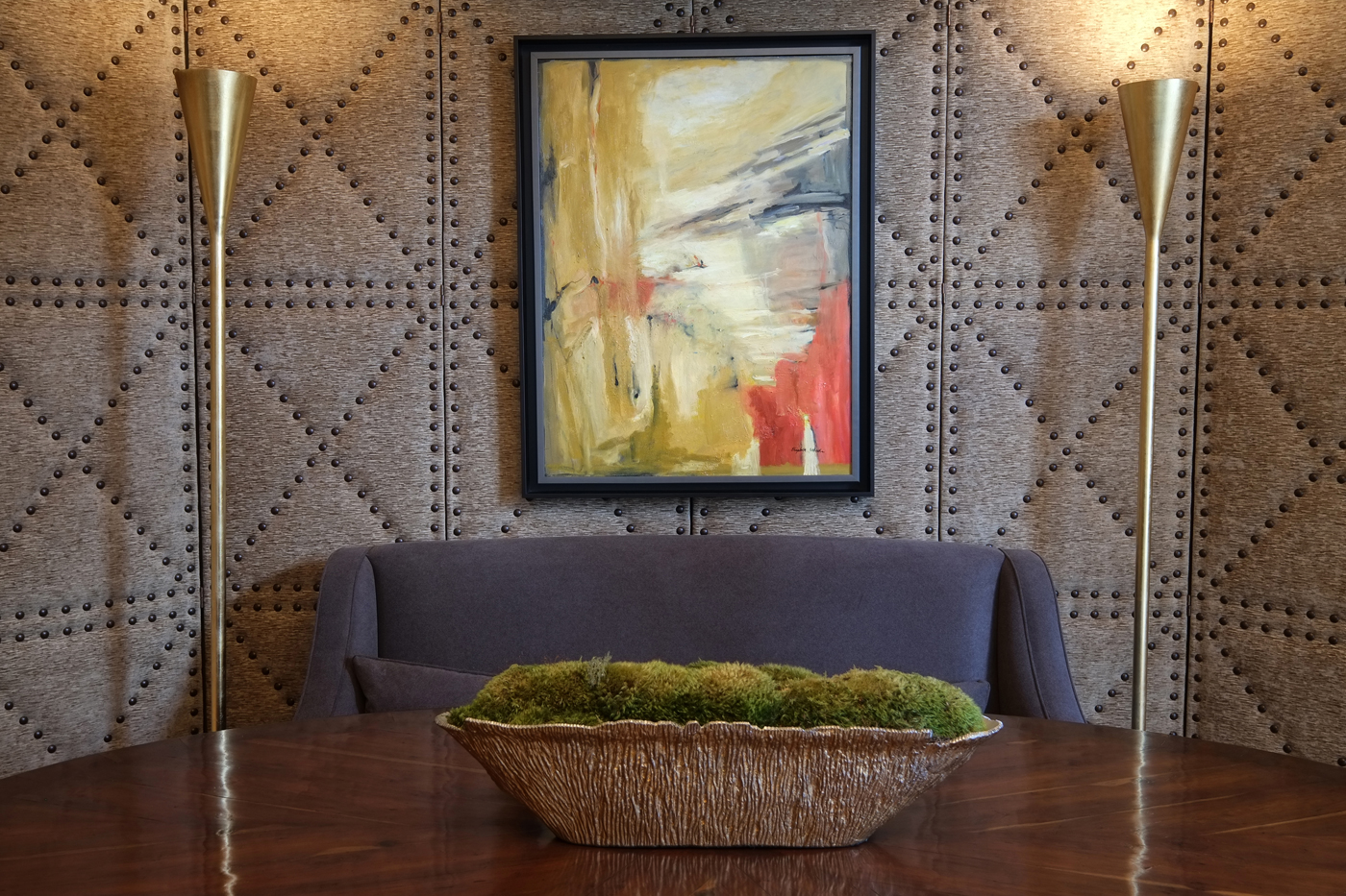 Upholstered and studded panel backdrop for floor-standing torchieres, settee, and abstract painting | Savage Interior Design