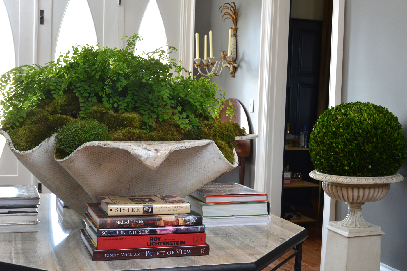 Centerpiece and decorative books top a custom iron center table designed by Jonathan Savage | Savage Interior Design
